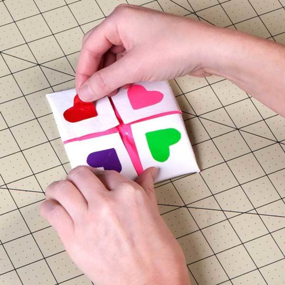 4 different colored Duck Tape heart cutouts placed on the small squares formed on the opposite side of the square