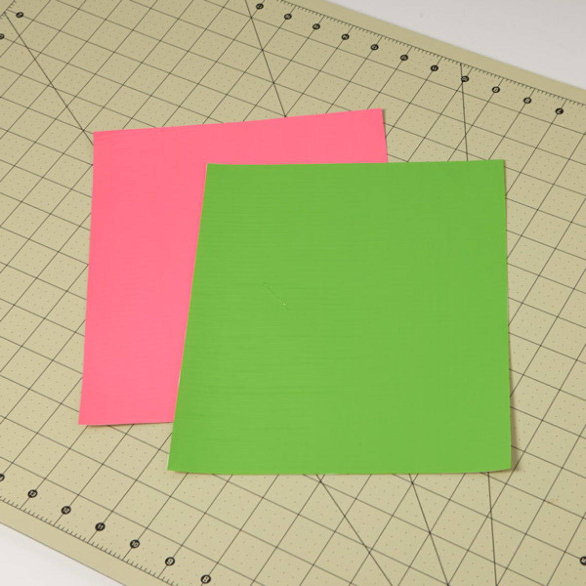 one pink and one green Duck Tape fabric sheet placed on a crafting board