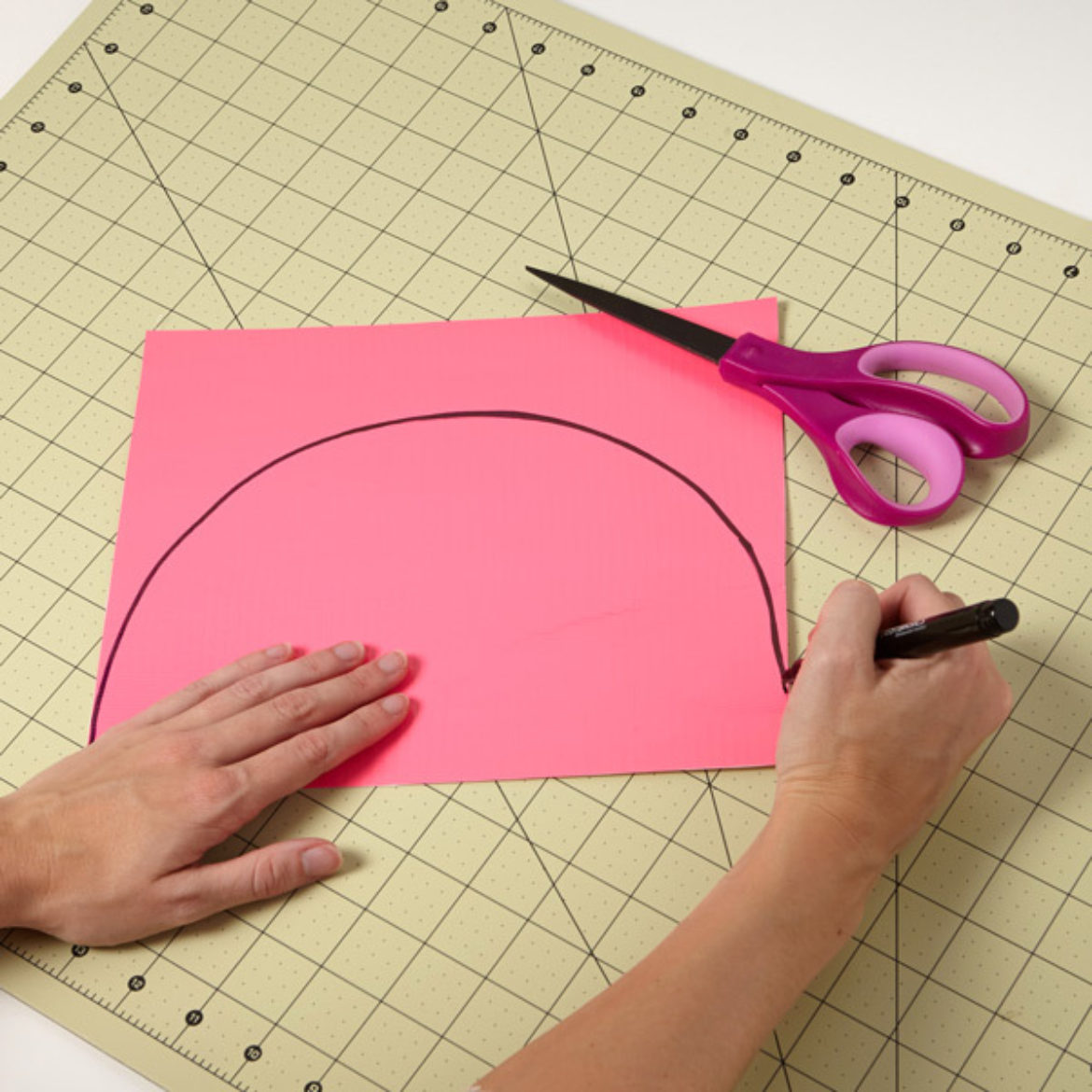Half circle being drawn on a pink sheet of Duck Tape fabric