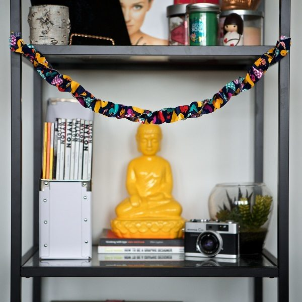 Completed Duck Tape® Garland hanging from a book shelf