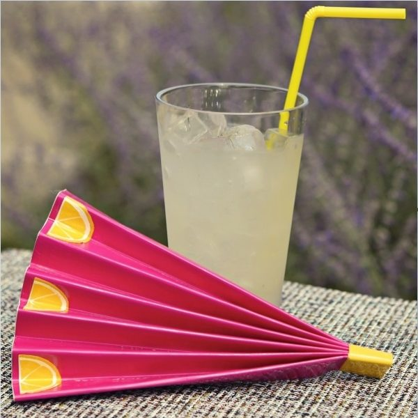 Completed Duck Tape®Hand Fan placed next to a glass of lemonade