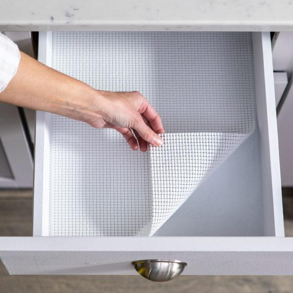 Hand lifting corner of white shelf liner in drawer