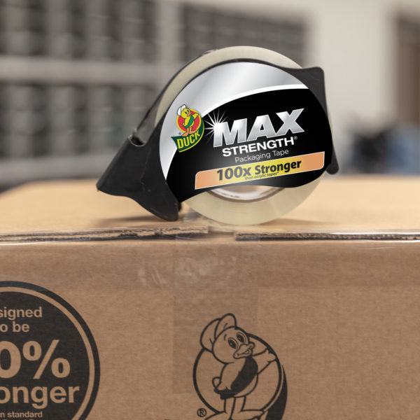 Duck Max Strength Packaging Tape in dispenser sitting on top of sealed brown corrugate box