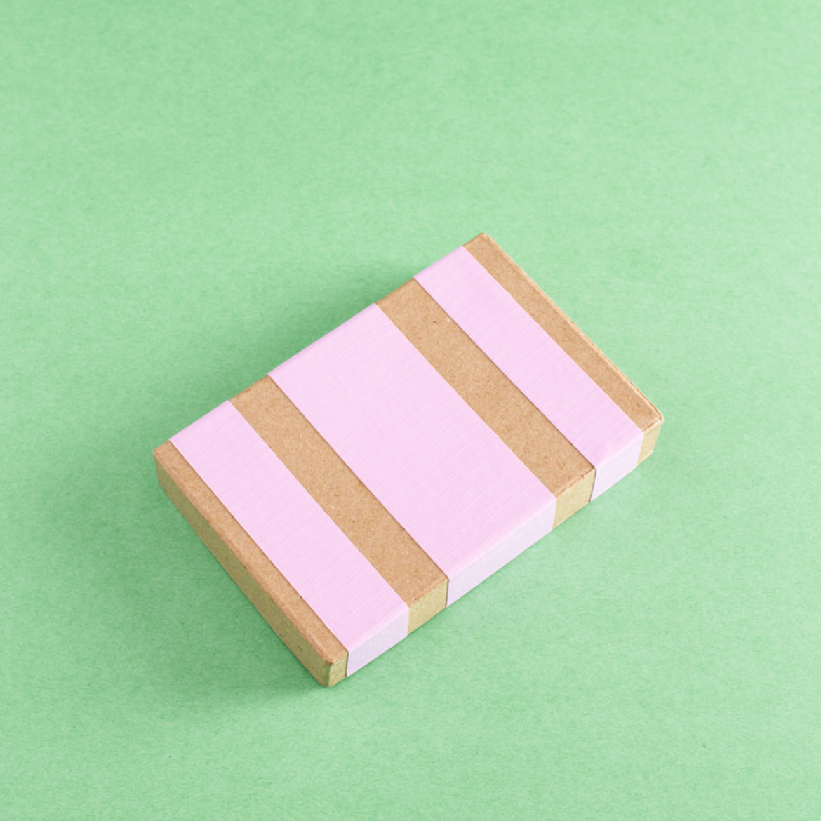 Strips of pink duct tape placed on paper mache box