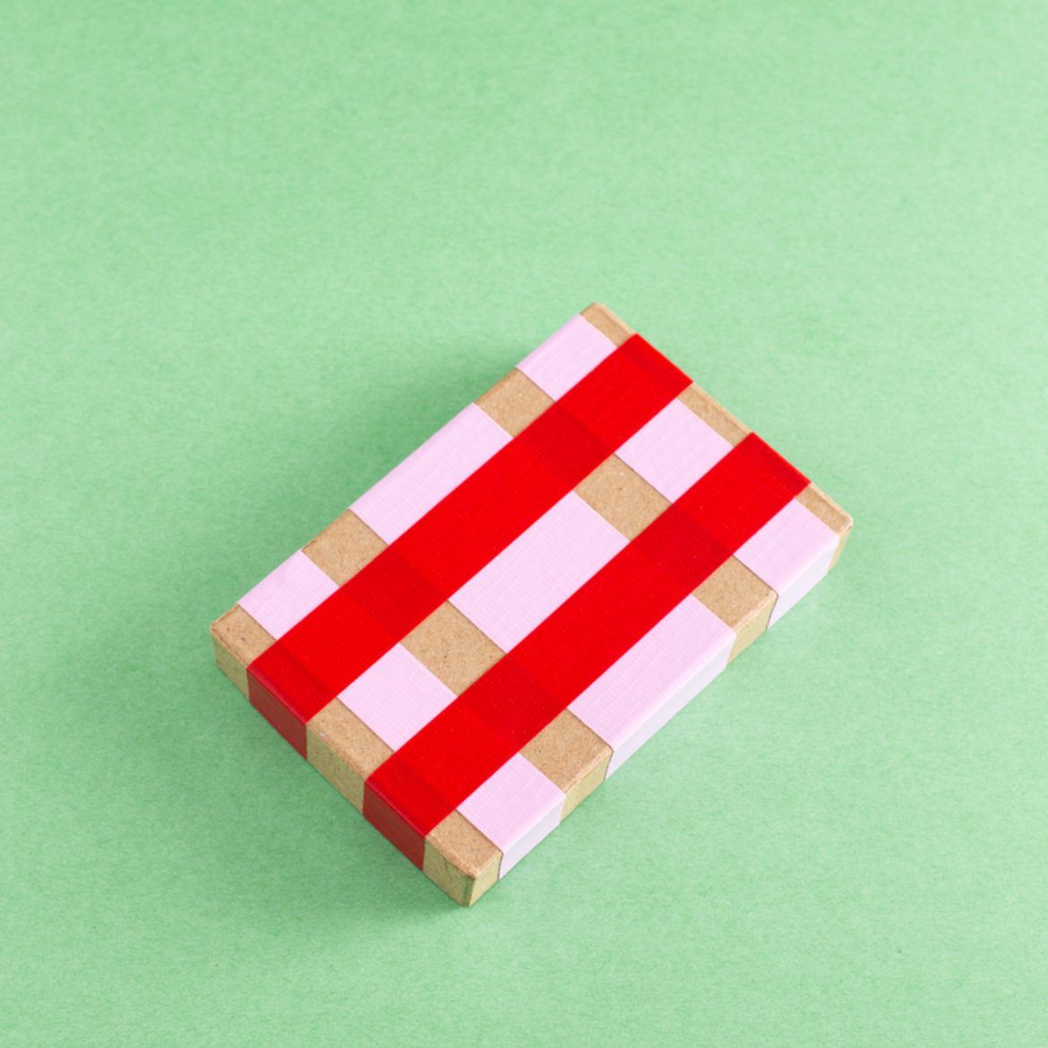 Strips of pink and red duct tape on a paper mache box