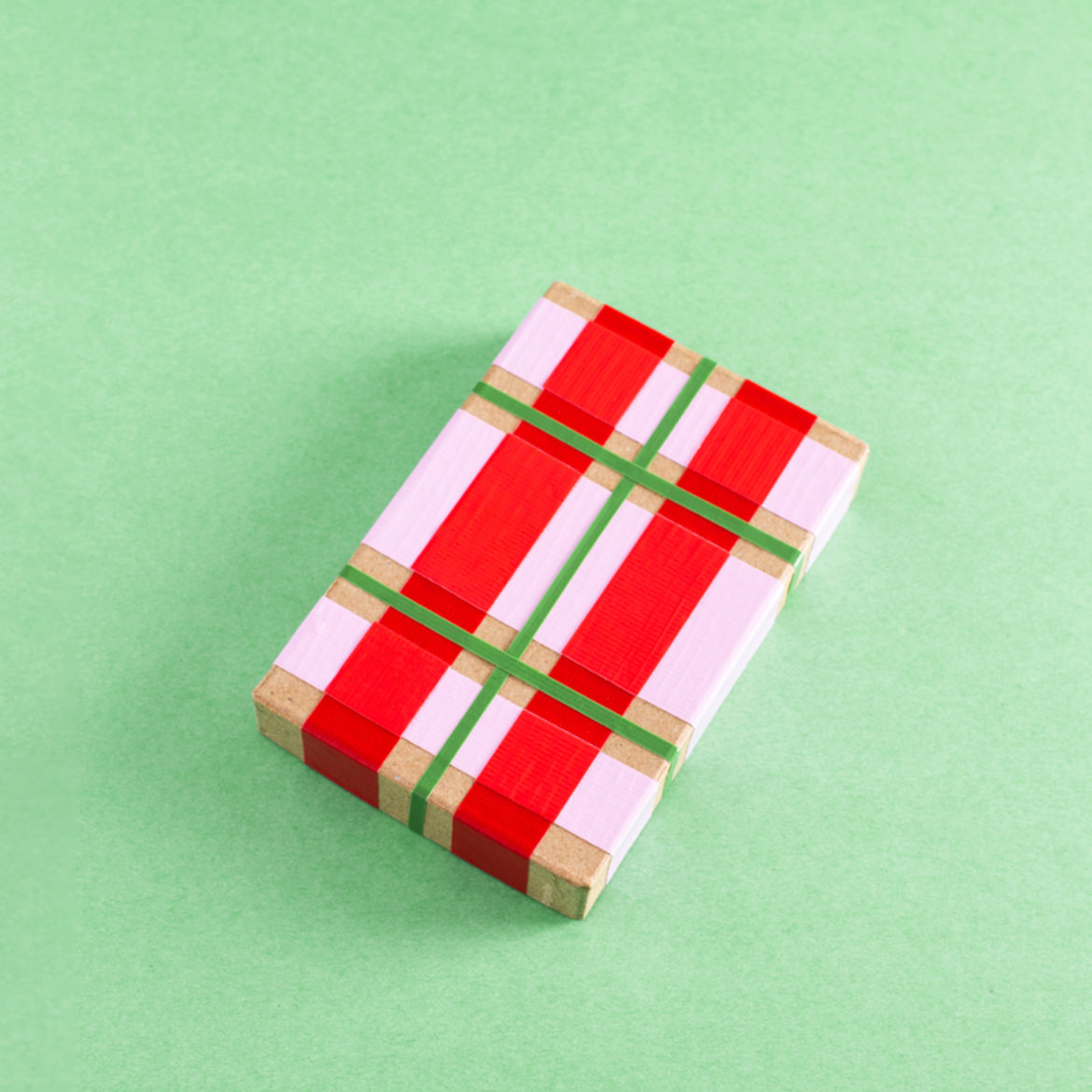 Strips of pink, red and green duct tape on a paper mache box