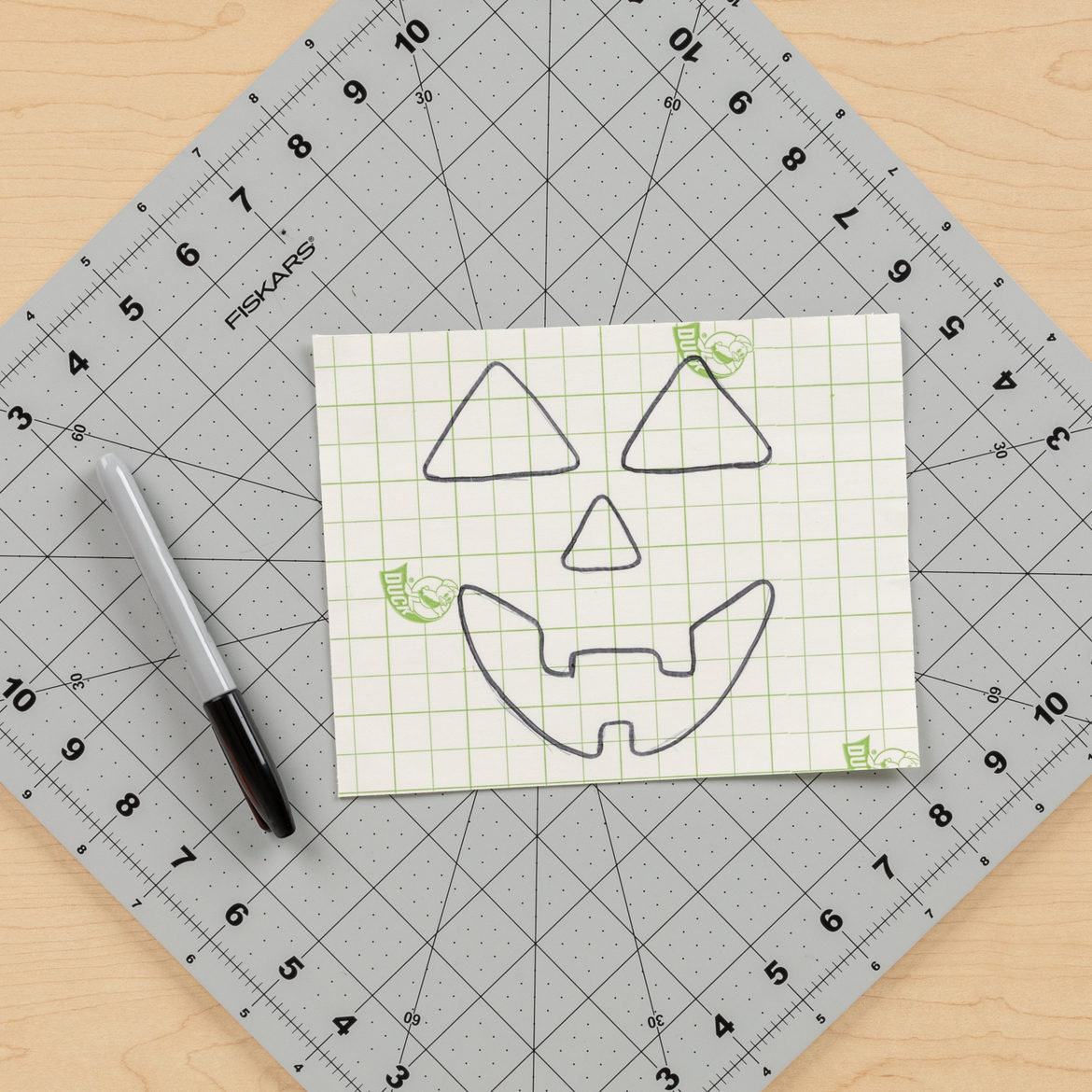 Pumpkin face drawn onto fabric from previous step