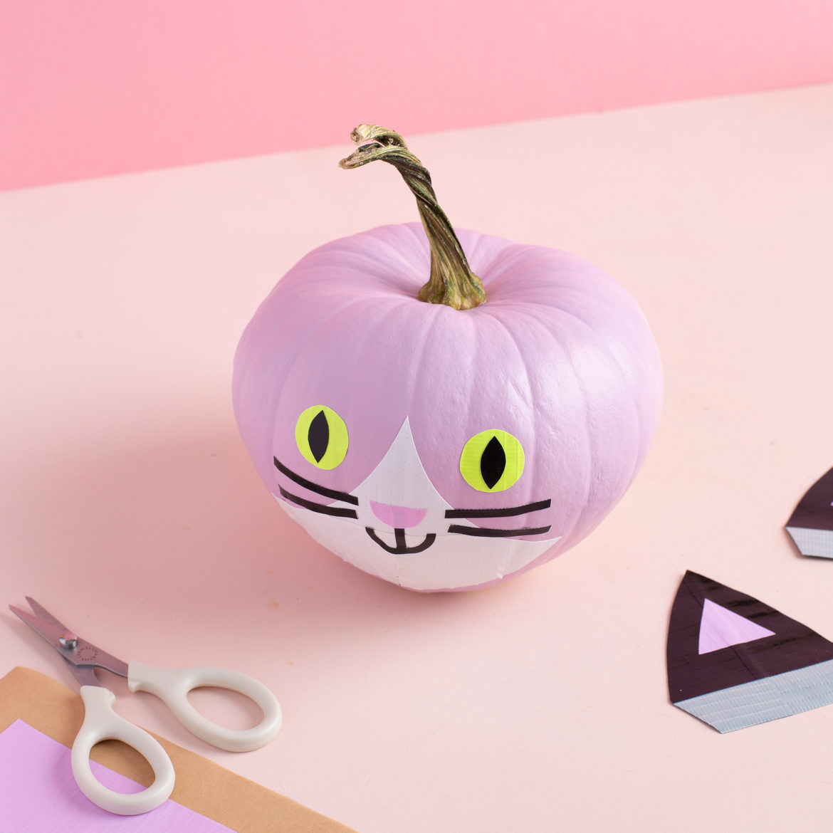 Duct tape cat face applied to painted pink pumpkin.
