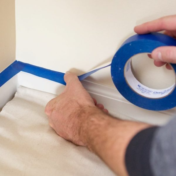Blue painters tape on a wall's edge