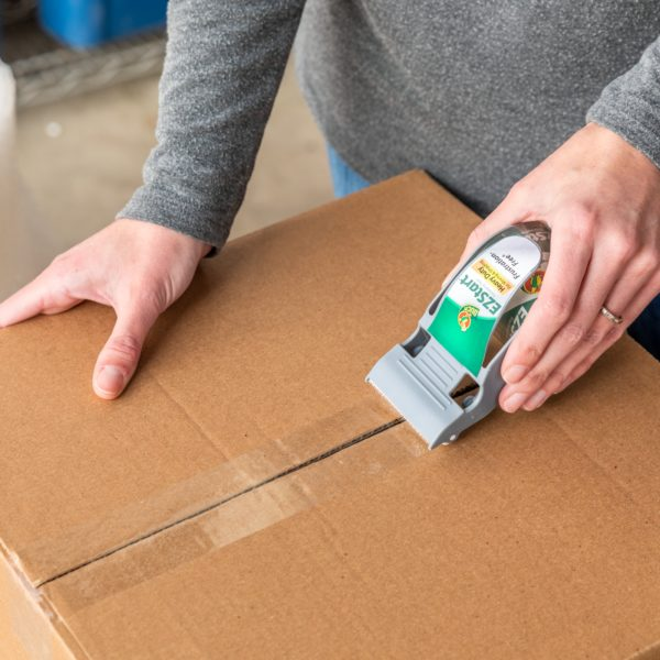 Woman using One-Handed EZ Start Dispenser to seal a brown corrugate box