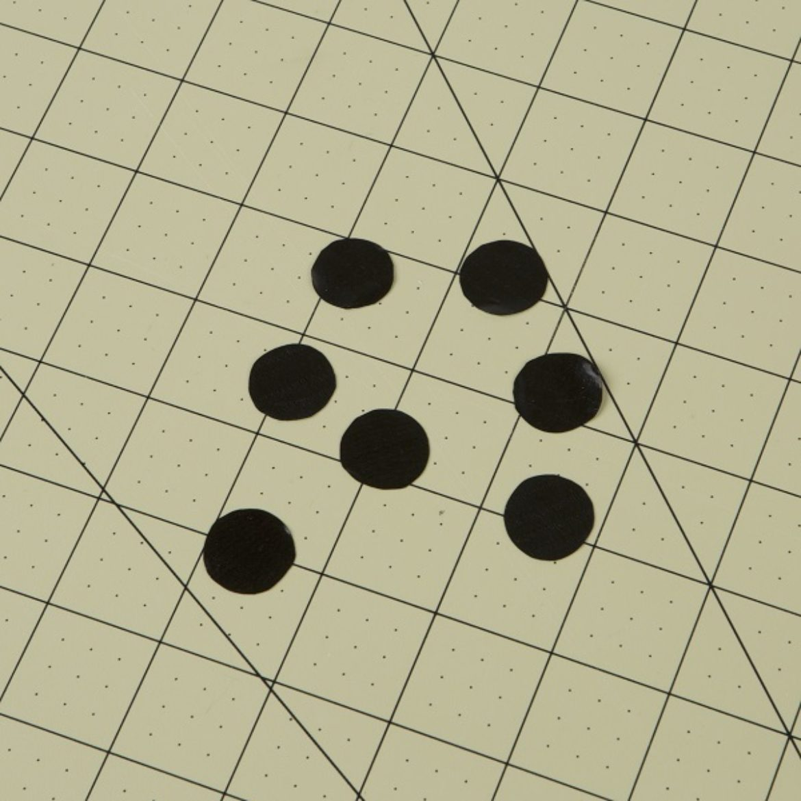 Small circles the size of a coin cut out of a Duck Tape Sheet