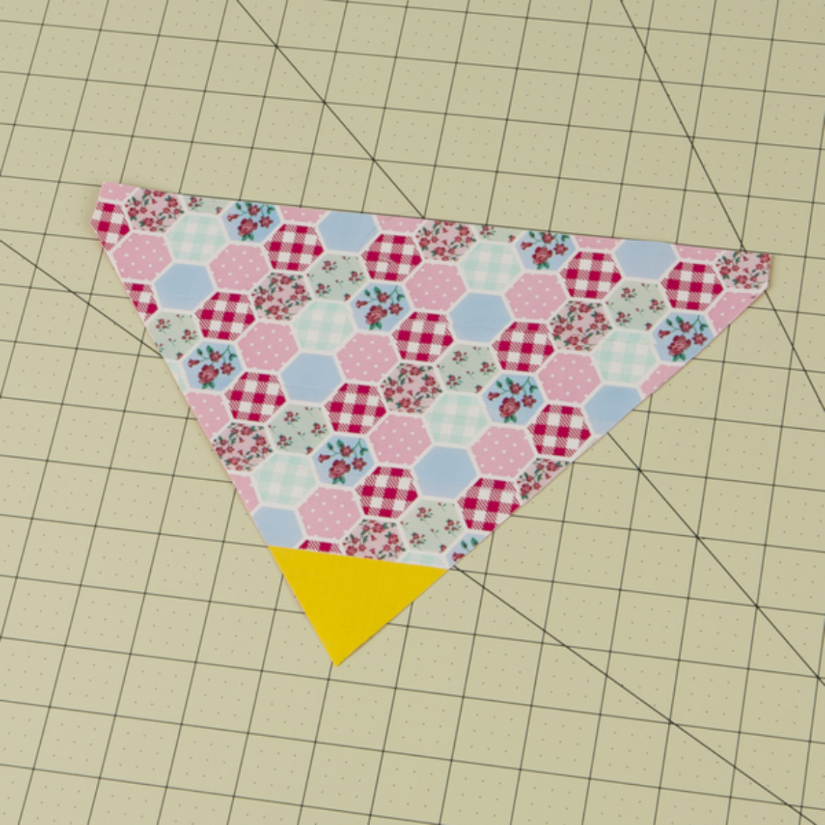 fabric from the prevoius step cut into a triangle so that there is a small triangle of yellow tape at the bottom