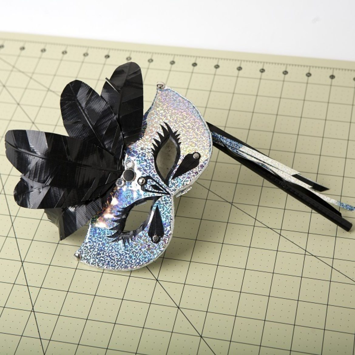Completed mask with multiple Duck Tape feathers and other embellishments