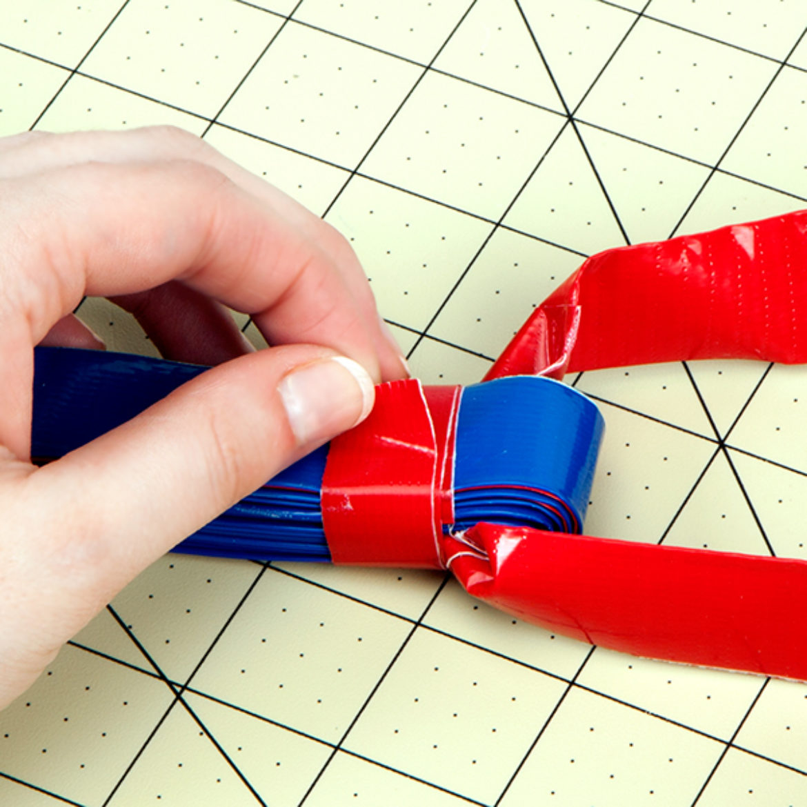 Double sided strips from step 1 folded in half with the handle made in step 3 in the center of the fold. Srtip of Duck Tape wrapped around the fold to hold it in place