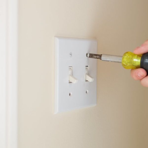 Removing a light switch cover from a wall.