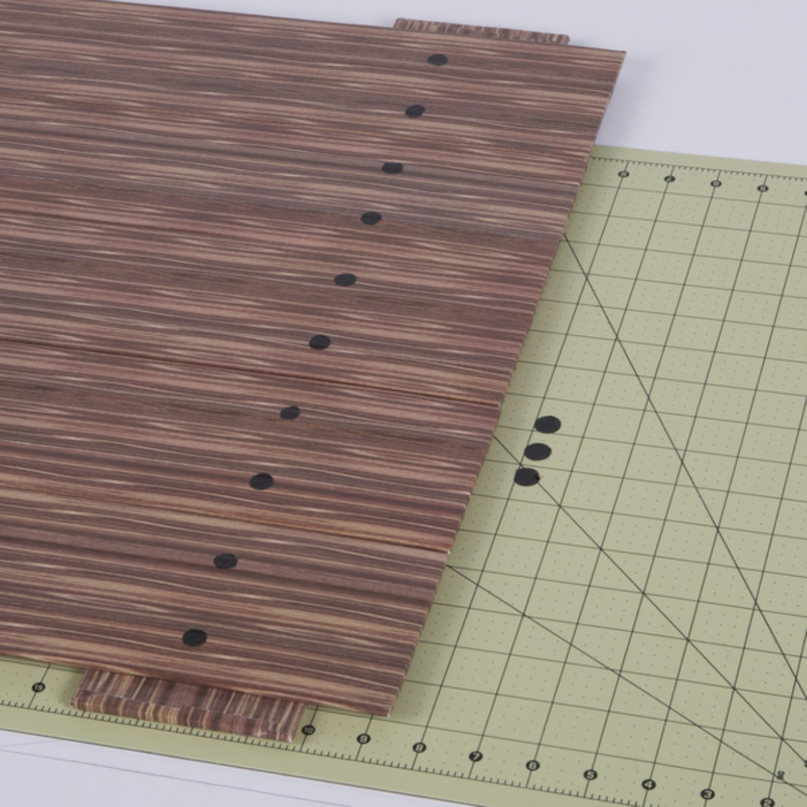 Small black Duck Tape circles plced on the front of the boards to look like nails in the wood