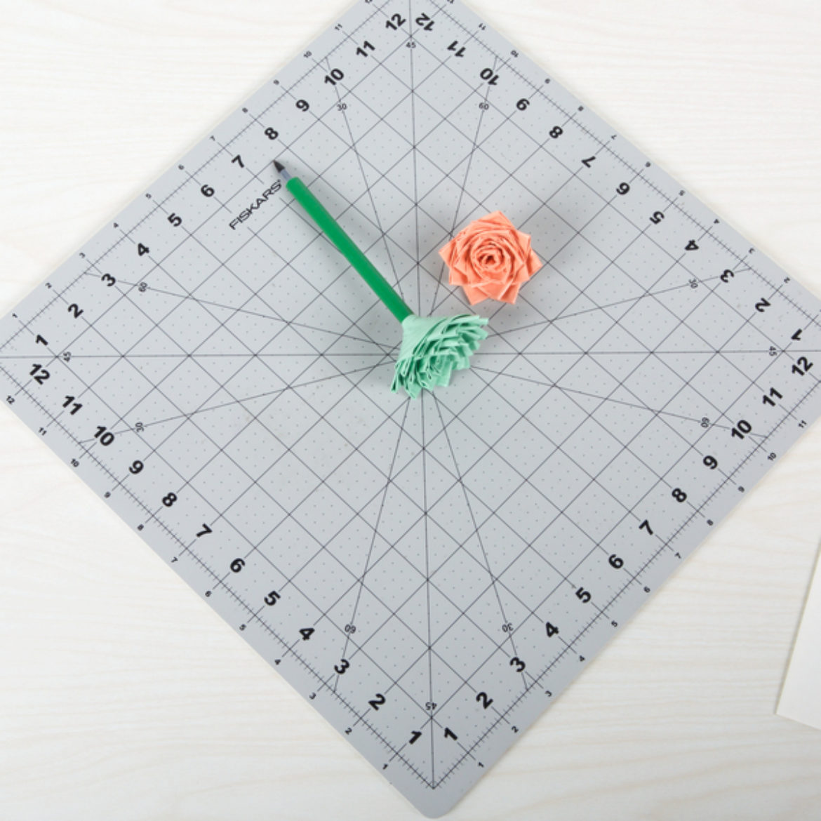 One green flower topping a pen and a pink flower placed on a crafting board