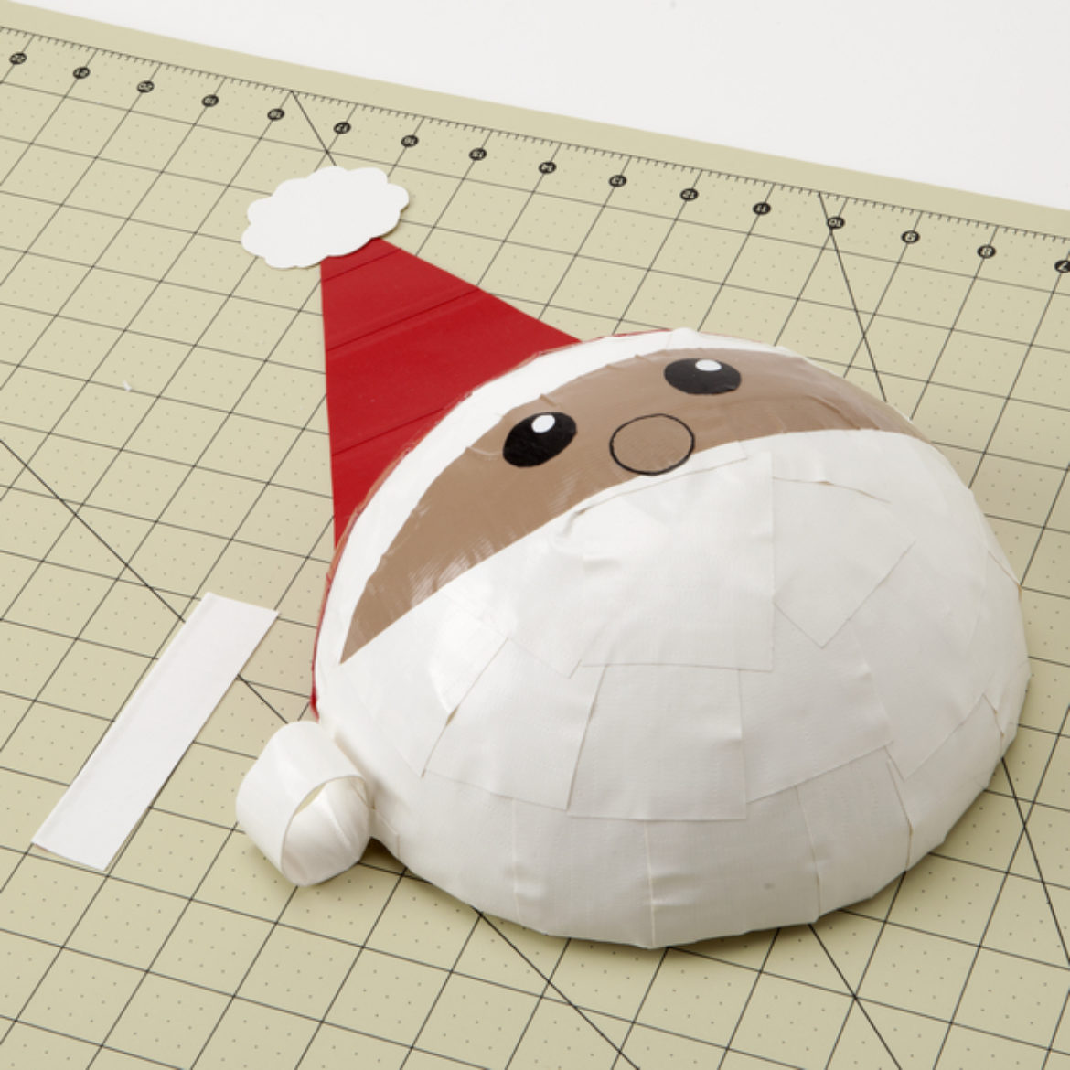 Strip from previous step formed into a loop, and then taped to the side of Santa's face to form the beard