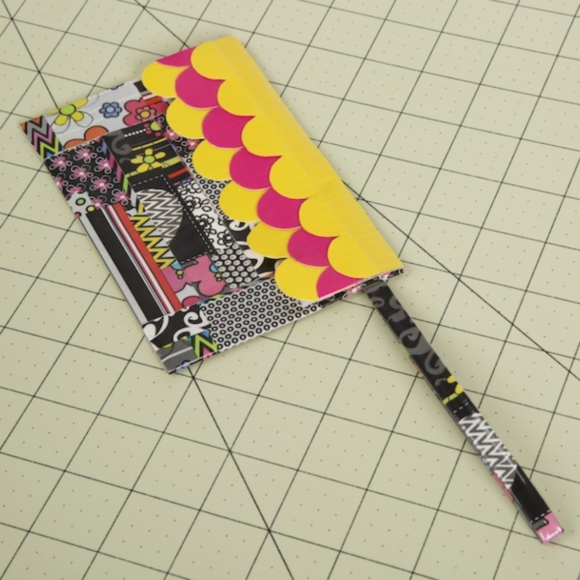 Thin double sided strip of Duck Tape folded over and attached to the corner of the wristlet
