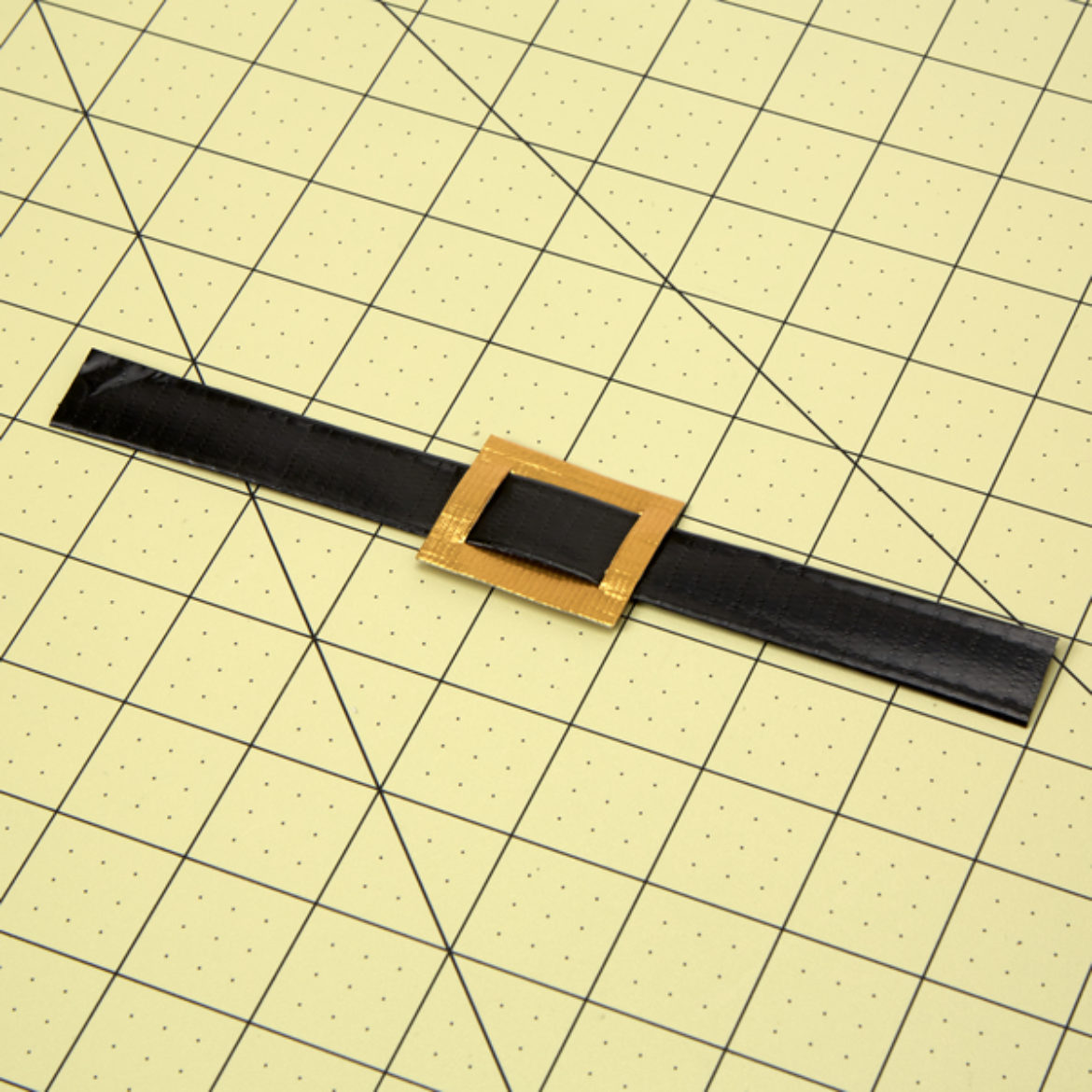 Cut two slits into the previous gold rectangle and feed the strap through to form a buckle and strap
