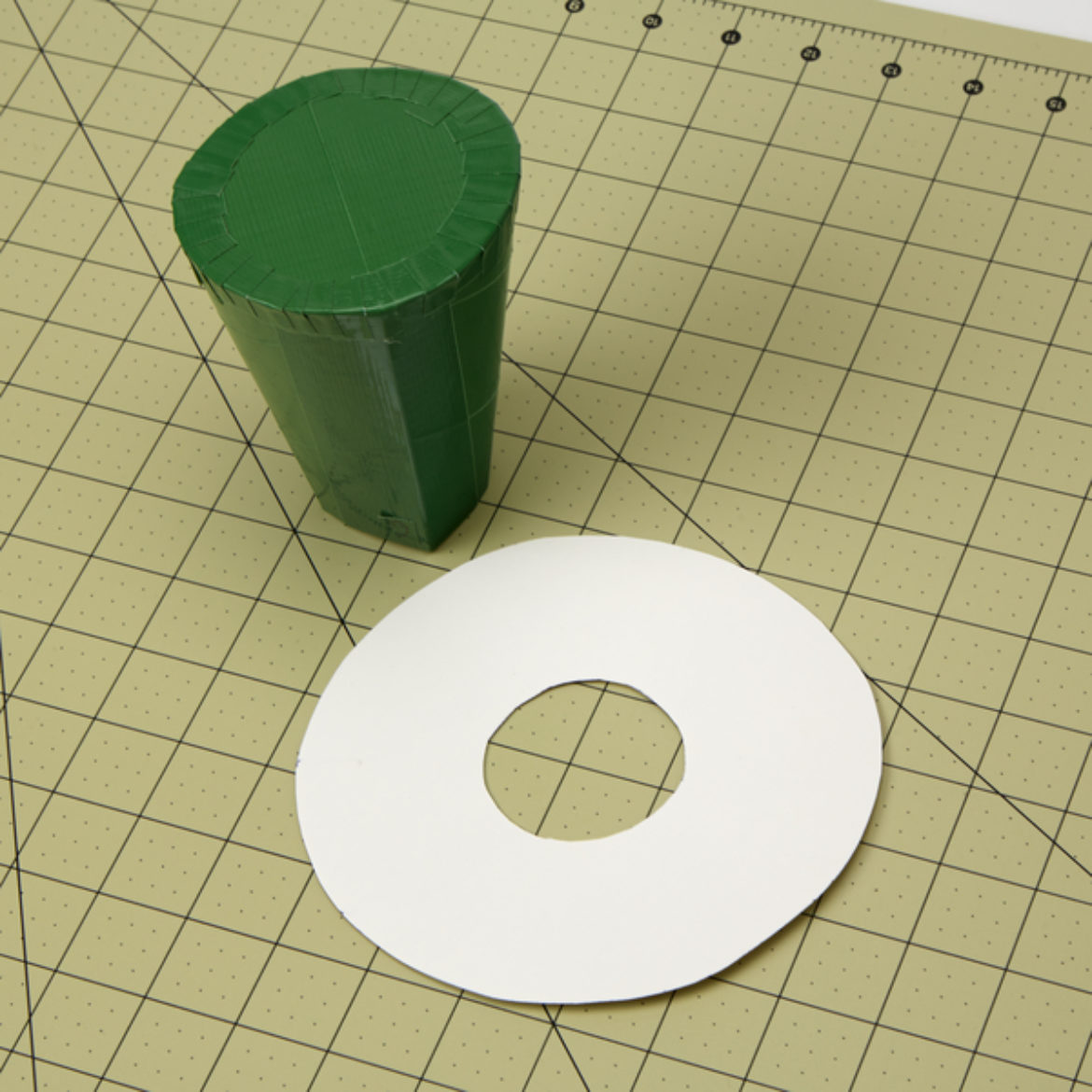 Donut shaped piece of poster board where the inner circle is the same diameter of the small circle of your cylinder