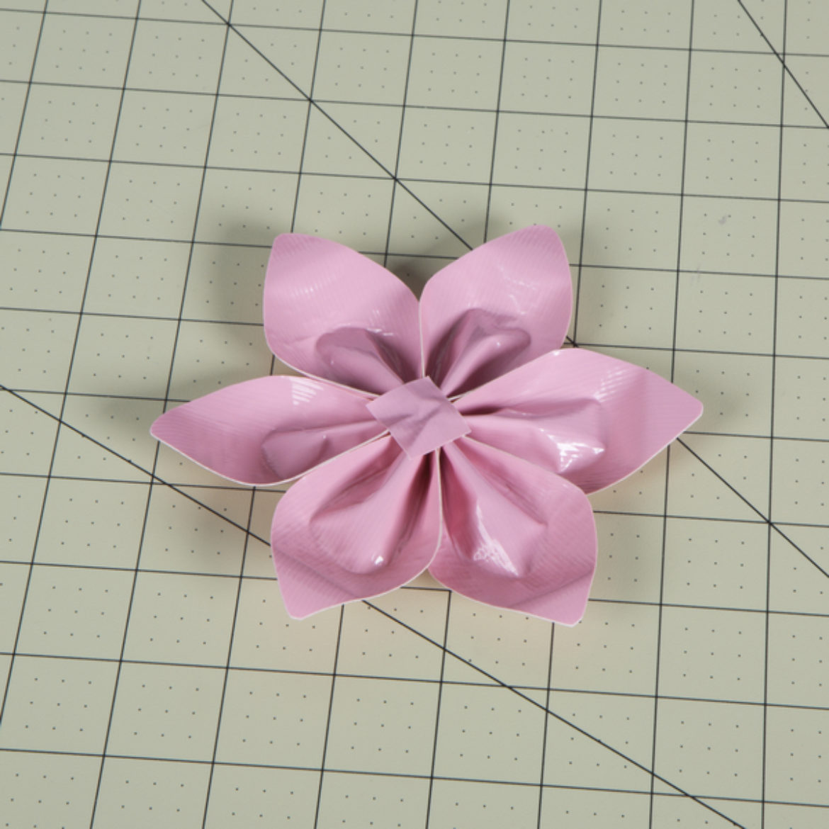 excess string cut off and taped into place on the back of the flower