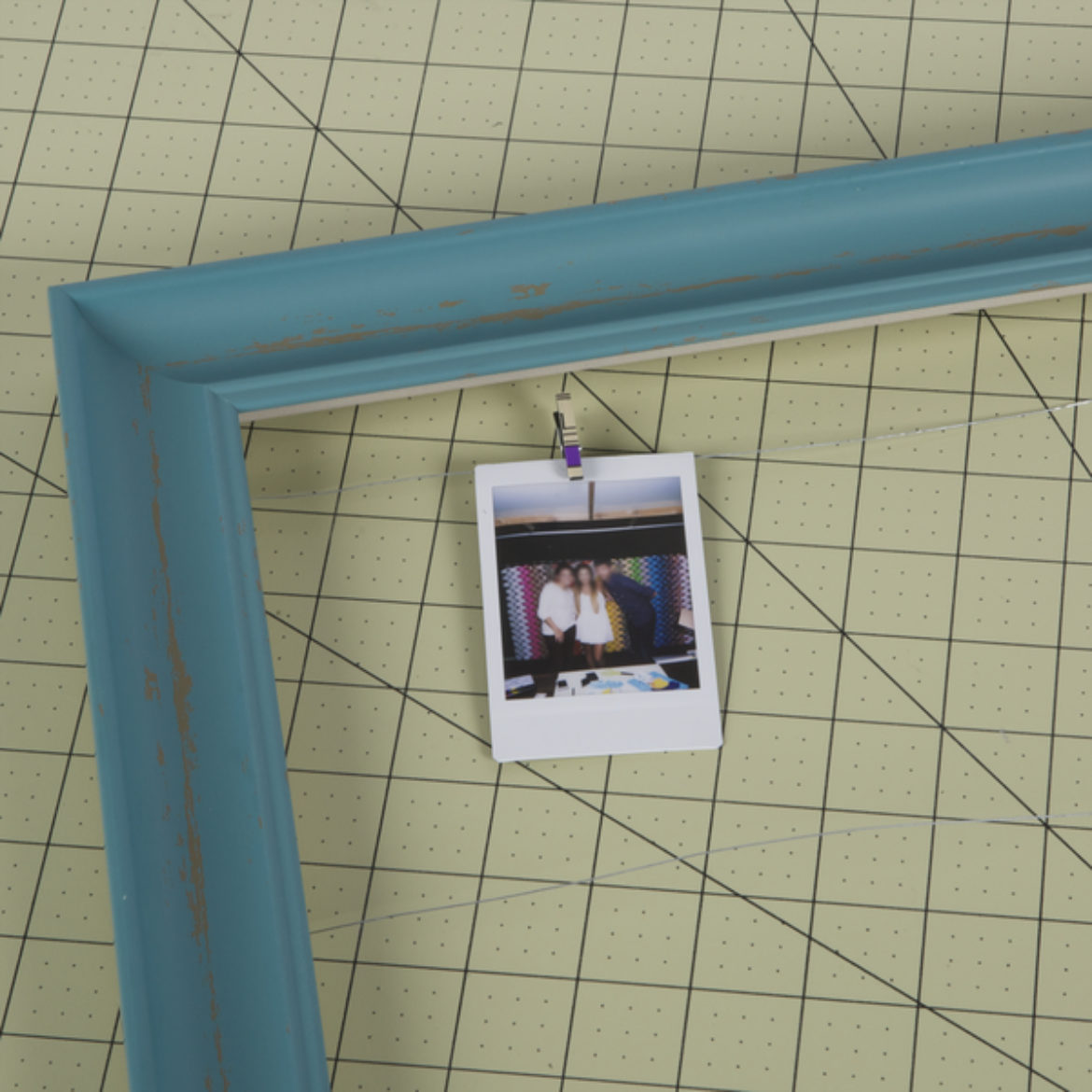 Letters and shapes attached to the frame, with a picture hung from the clothes pin that is attached to the wire strung across the frame