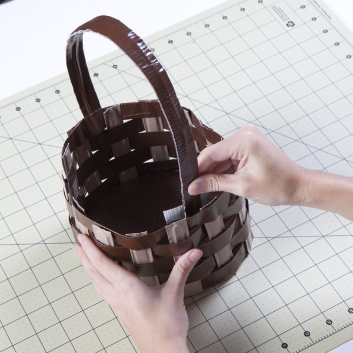 Handle fashioned from a double sided strip of Duck Tape being taped to the inside of the basket